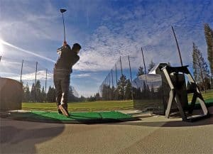 Golfer swinging next to Range Servant Automatic Bay Divider
